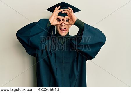 Young caucasian man wearing graduation cap and ceremony robe doing ok gesture like binoculars sticking tongue out, eyes looking through fingers. crazy expression.