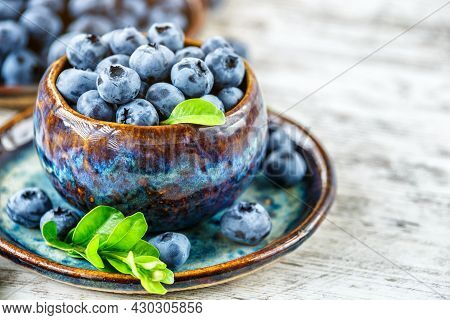 Fresh Blueberries Background With Copy Space For Your Text.blueberries In A Bowl On A Wooden Table.