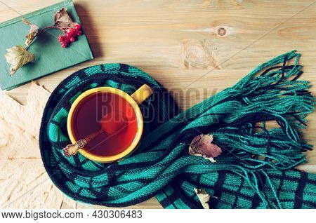 Autumn background - cup of tea, old book and warm scarf on the wooden background. Autumn still life. Still life with concept of spending autumn time at cozy home, autumn composition, autumn still life, autumn design