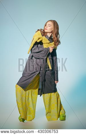 Fashion model girl poses in stylish clothes from the spring-summer collection. Haute couture clothing. Full length studio portrait.