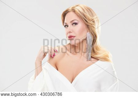 Beautiful sexy middle aged woman with enlarged full lips and evening makeup posing in precious jewelry. White background. Beauty and jewelry.