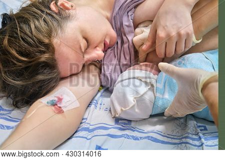The First Breast Feeding Of A Newborn Baby Boy Immediately After Giving Birth On A Hospital Bed In A