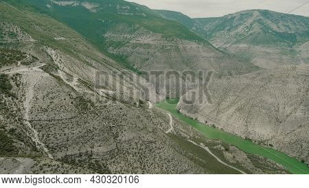 Top View Of Mountain Slopes With Dangerous Roads. Action. Winding Roads On Slopes Of Green Mountains