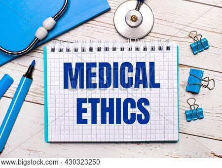 On A Light Wooden Background, A Stethoscope, A Blue Notepad, Blue Paper Clips, A Blue Marker And A S