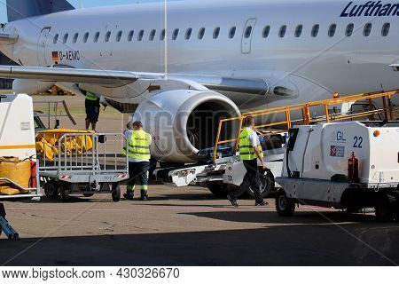 Belgrade, Serbia - August 08, 2017: Ramp Handling Employee Loading Cargo Packages On Plane Platform