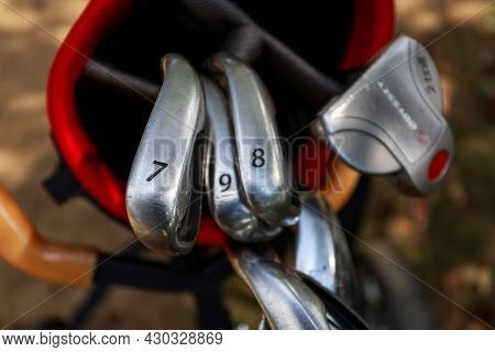 Minsk. Belarus - 25.07.2021 - Golf Clubs In A Red Bag Close-up Green Grass Background
