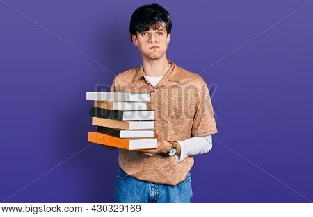 Handsome hipster young man holding a pile of books puffing cheeks with funny face. mouth inflated with air, catching air.