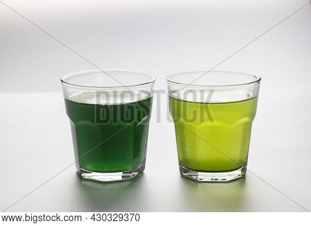 Dissolved Powder Spirulina And Chlorella In A Transparent Glass Cups On White Background.