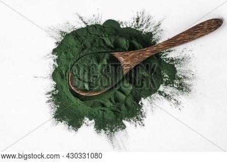 Organic Spirulina Algae Powder In Wooden Spoon On White Background. Top View