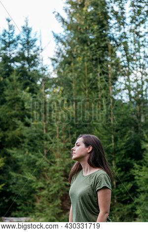 Young Woman In Forest. Portrait Of A Young Caucasian Girl In Profile Against Background Of Trees, Fi