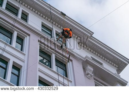 Wellington New Zealand - July 29 2021; Roped Up Abseiling The Side Of High Building Cleaner Is Worki