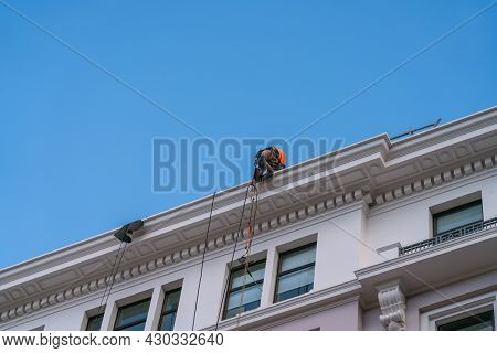 Wellington New Zealand - July 29 2021; Roped Up And On The Edge Of High Roof Of Building A Building