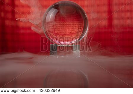 Crystal Ball Reflecting A Red Background And Falling Smoke, Selective Focus.