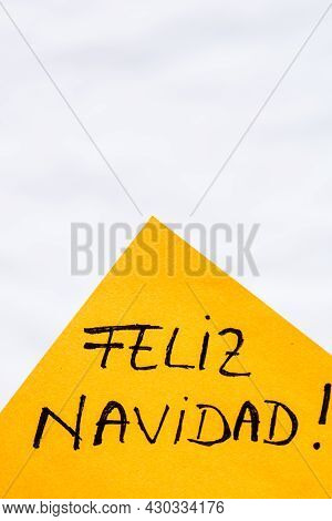 Feliz Navidad (merry Christmas) Handwriting Text Close Up Isolated On Orange Paper With Copy Space.