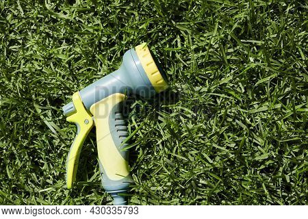 On The Green Lawn There Is A Hose For Watering Plants. A Water Hose With A Sprayer For Watering Plan