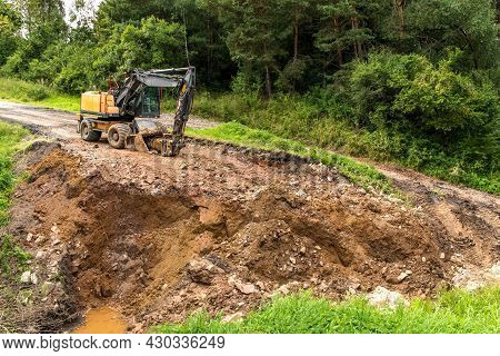 A Large Construction Excavator Of Orange Color On A Road Construction Site In The Czech Countryside.
