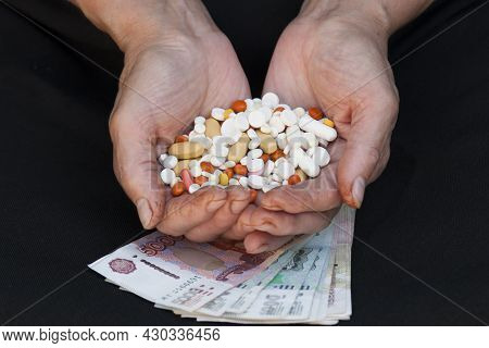 A Handful Of Various Pills In Female Hands Over Black Background And Russian Money
