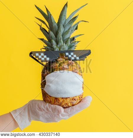 Funny Pineapple Face In Protective Medical Mask. Doctor Hand In Rubber Glove Holds Summer Tropical F
