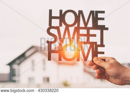 Hand holds wooden phrase Home sweet home in front of  blurred house. Concept of buying or building home of dreams