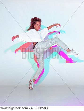 Dancing Mixed Race Young Girl In Colourful Light. Female Dancer Performer Showing Hip Hop Expressive