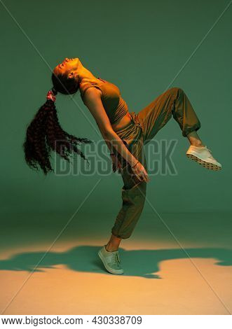 Dancing Athletic Mixed Race Girl Performing Expressive Fiery Hip Hop Or Ethnic Afro Dance In Studio