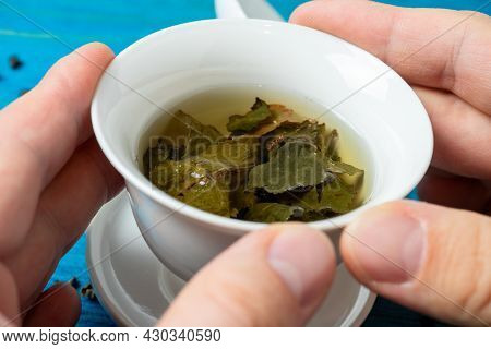 In Man Hands Is A White Porcelain Bowl With Fresh Tea On A Blue Wooden Background. The Opened Leaves