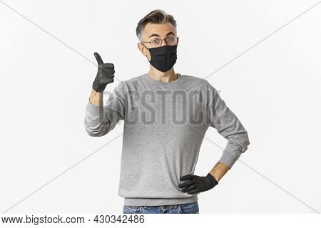 Covid-19, Pandemic And Social Distancing Concept. Portrait Of Satisfied Middle-aged Man In Black Med