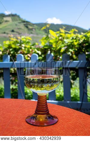 White Quality Riesling Wine Served In Yellow Swirl Wine Glass On Outdoor Terrace In Mosel Wine Regio