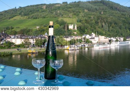 White Quality Riesling Wine Served On Old Bridge Across Mosel River With View On Old German Town In