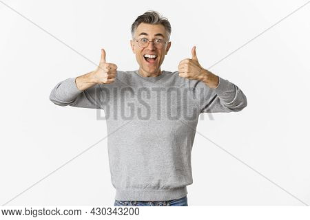 Portrait Of Handsome Middle-aged Man In Glasses And Grey Sweater, Looking Excited And Smiling, Showi
