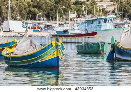 Traditional Luzzu boat at Marsaxlokk harbor a fishing village located in the south-eastern part of Malta. poster