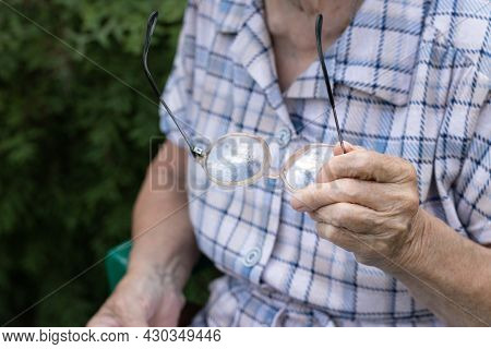 Senior Woman Sitting On Nature And Holding Glasses On Hand, Close Up, Faceless