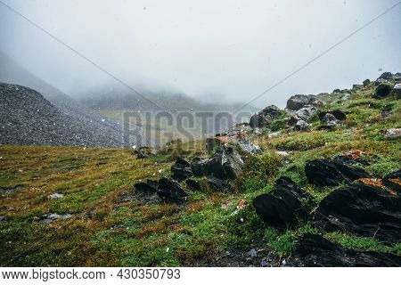 Beautiful Snowfall In High Mountains. Pointy Rocks On Hill During Snowfall. Scenic Landscape With Fl