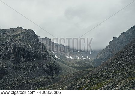 Dark Atmospheric Mountain Landscape With Gray Low Clouds In Dark Valley In High Altitude In Rainy We