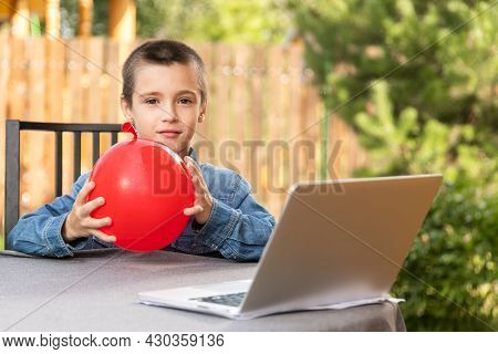 A Boy  Inflates  Red Balloon On A Warm Summer Day In The Garden. Birthday Preparation