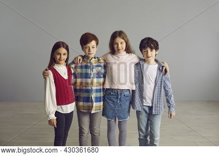 Schoolkid Friends Standing Together In Row Hugging Looking At Camera Studio Shot