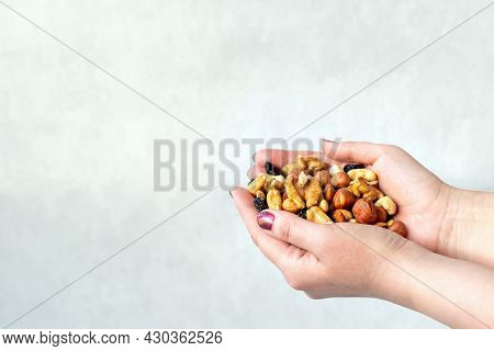 Close Up And Soft Focus Of A Woman's Hand With Nuts And Raisins On The Light Grey Background. The Co