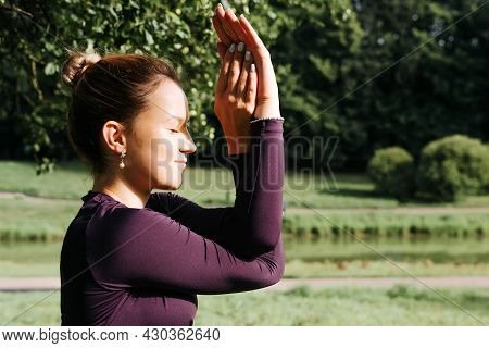 Profile Portrait Of Young Smiling Woman Practicing Yoga And Meditation Outdoors, Performing An Asana