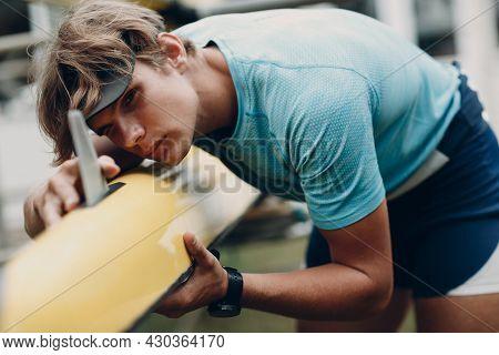 Sportsman Single Scull Man Rower Sportsman Check His Boat. Caucasian Sportsman Checking His Canoe Bo