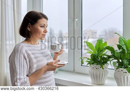 Serious Middle Aged Woman Looking Out The Window
