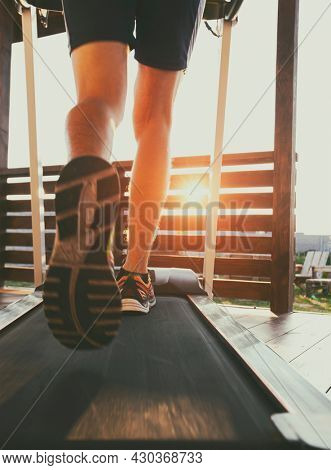 The guy jogging on treadmill on terrace of his home. Social isolation or quarantine concept