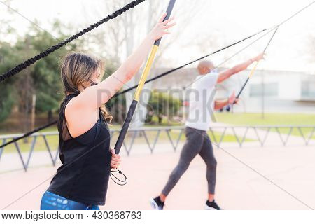 Side View Of Fitness Couple Exercising With A Fitness Strap In The Park.