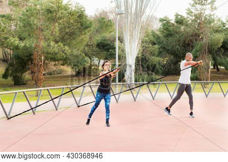 Fitness Couple Exercising With A Fitness Strap In The Park