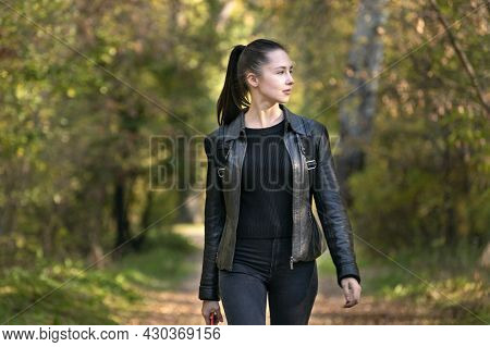 Stylish Young Woman Walks In The Autumn Park. Beautiful Girl In Black Clothes In The Forest. Alley,