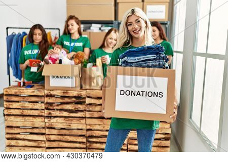 Group of young volunteers woman smiling happy working at charity center.