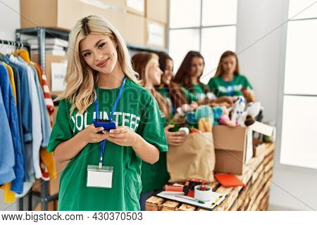Group of young volunteers woman working at charity center. Girl smiling happy using smartphone.