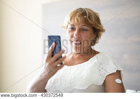 Woman Testing Glucose Level With Continuous Glucose Monitor On Mobile Phone