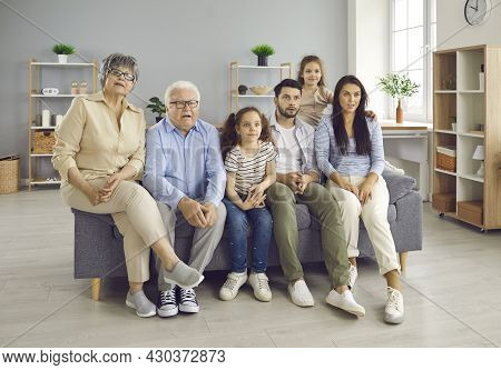 Home Portrait Of Big Family With Grandparents And Kids Showing Amazed Emotion