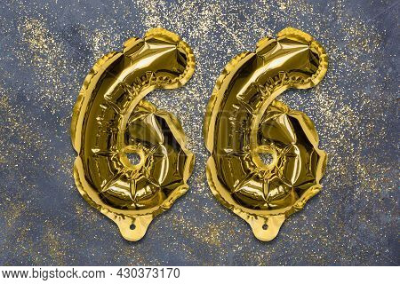 The Number Of The Balloon Made Of Golden Foil, The Number Sixty-six On A Gray Background With Sequin