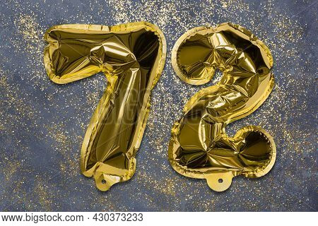 The Number Of The Balloon Made Of Golden Foil, The Number Seventy-two On A Gray Background With Sequ